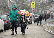 On the first day of Spring, snow flakes surround parents and children at the end of the school day on Friday, March 20, 2015, in Bayside, N.Y.