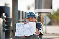 Portrait of a homeless person with sign paper