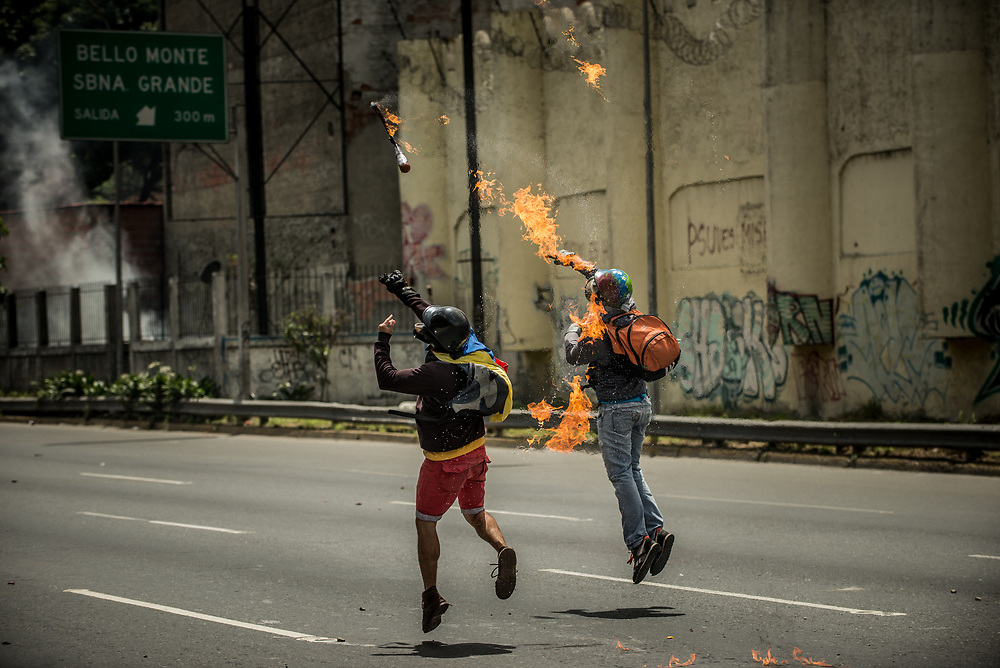 CARACAS, VENEZUELA - MAY 26, 2017:  Anti-government protesters hurl  molotov cocktails during clashes with members of the National Police for control of the main highway that runs through Caracas. Authorities responded by heavily tear gassing and firing rubber bullets and buckshot at them. The streets of Caracas and other cities across Venezuela have been filled with tens of thousands of demonstrators for nearly 100 days of massive protests, held since April 1st. Protesters are enraged at the government for becoming an increasingly repressive, authoritarian regime that has delayed elections, used armed government loyalist to threaten dissidents, called for the Constitution to be re-written to favor them, jailed and tortured protesters and members of the political opposition, and whose corruption and failed economic policy has caused the current economic crisis that has led to widespread food and medicine shortages across the country.  Independent local media report nearly 100 people have been killed during protests and protest-related riots and looting.  The government currently only officially reports 75 deaths.  Over 2,000 people have been injured, and over 3,000 protesters have been detained by authorities.  PHOTO: Meridith Kohut