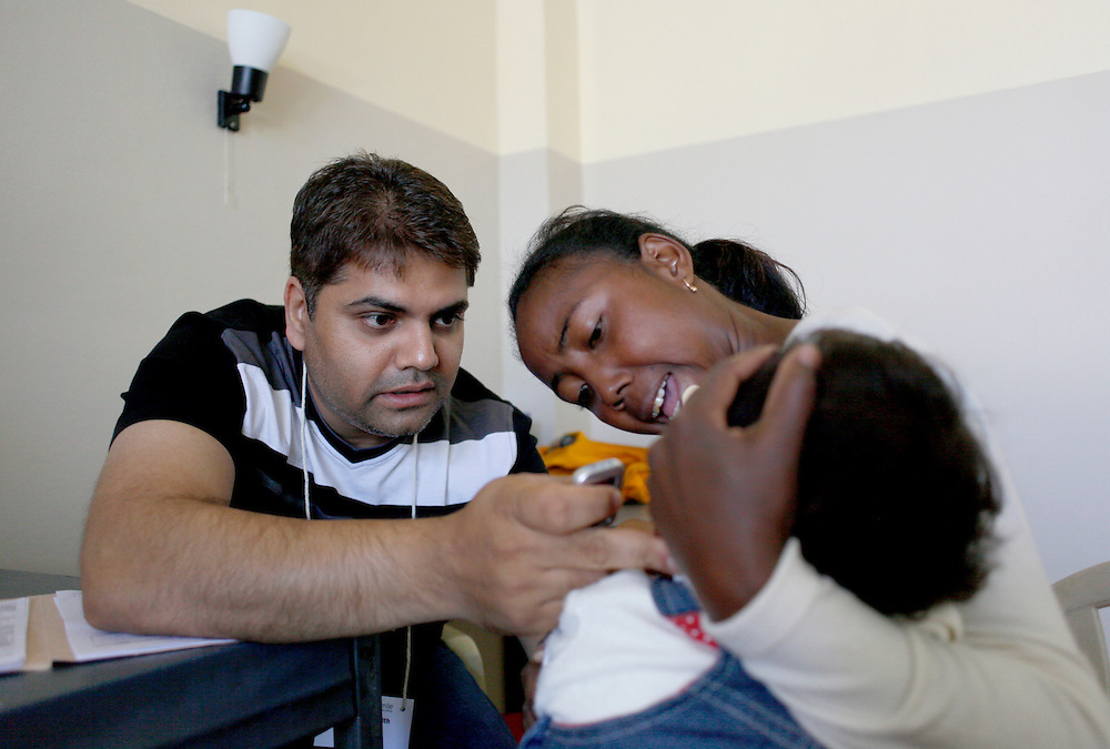 Dentist Alankar Ranjith from Durban, South Africa examines a patient during the screening process on Day Two...Operation Smile South Africa.Operation Smile Mission to Hospital Joseph Ravoanangy Andrianavalona,.Antananarivo, Madagascar. September 17th - 29th 2011..© Operation Smile Photo / Zute & Demelza Lightfoot.www.lightfootphoto.com
