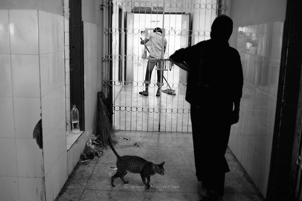 A cat roaming the waiting room while a woman stands outside the gate of the gynae ward and staff are cleaning the floor. Hygiene still is one of the biggest problems in most health facilities in Pakistan. Qatar hospital, Karachi, Pakistan 2010