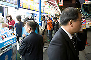 businessman talking on his cell phone outside an electronics store in Tokyo