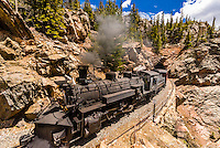 The Cumbres & Toltec Scenic Railroad train pulled by a steam locomotive comes out of a tunnel at 9669 feet on the 64 mile run between Antonito, Colorado and Chama, New Mexico.