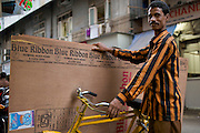 Building supply delivery man on Modi Street in the Fort Market outside of Gulshan Haircutting Salon.  He's riding a classic style, double top tube design Hercules utility bike - Bombay/Mumbai - India