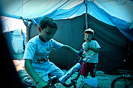 Syrian children play on bicycles in a refugee camp in Turkey's southern province of Hatay, neighbouring Syria. Yayladagi, Turkey. 11/06/2012