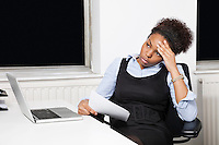 Tired young businesswoman in front of laptop at desk in office