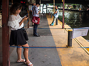 15 SEPTEMBER 2017 - BANGKOK, THAILAND: Passengers wait to board a Khlong Saen Saeb passenger boat at the Asok Pier, on Sukhumvit Soi 21. Tens of thousands of passengers ride the boat every day, commuting into Bangkok from the eastern suburbs.      PHOTO BY JACK KURTZ