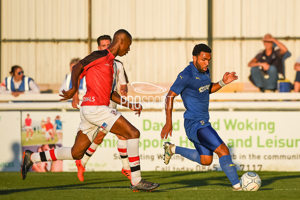 AFC Wimbledon Midfielder Andy Barcham (17) and Woking Defender Louis Ramsay (2) battle for the ball during the Pre-Season Friendly match between Woking and AFC Wimbledon at the Kingfield Stadium, Woking, United Kingdom on 10 July 2018. Picture by Stephen Wright.