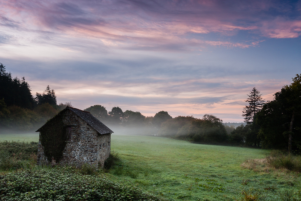 A small stone hut stands at a grass field as the morning mist rises near Broceliande Forest.