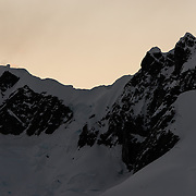 Rugged mountains at Paradise Harbor, Antarctica, are silhouetted against the setting sun.