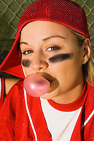 Softball Player Blowing Bubble in Dugout