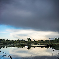 Rural landscape with scenic view across lake to trees and storm clouds in summer