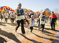"""Jessica Beane, Addison Beane and Monica Acken hold hands as they charge into the water with the Bank of NH """"Bananas"""" team during the 11th annual Turkey Plunge for the Salvation Army on Saturday afternoon at Lake Opechee.  (Karen Bobotas/for the Laconia Daily Sun)"""