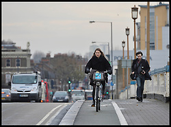 A lady ring a Boris Bike over Wandsworth Bridge, South West London, United Kingdom. Friday, 13th December 2013. Picture by Andrew Parsons / i-Images