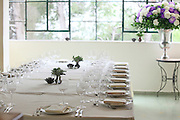 Festive table setting with white table cloth and flowers