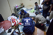 "Oct. 1, 2009 -- BANGKOK, THAILAND: Medics and volunteers from Poh Teck Tung help a woman who attempted suicide after an argument with her husband. Neighbors said the woman swallowed mosquito poison. She was unconscious and unresponsive and the crew rushed her to a nearby hospital. They left before getting final word on her status.  The 1,000 plus volunteers of the Poh Teck Tung Foundation are really Bangkok's first responders. Famous because they pick up the dead bodies after murders, traffic accidents, suicides and other unplanned, often violent deaths, they really do much more. Their medics respond to medical emergencies, from minor bumps and scrapes to major trauma. Their technicians respond to building collapses and traffic accidents with heavy equipment and the ""Jaws of Life"" and their divers respond to accidents in the rivers and khlongs of Bangkok. The organization was founded by Chinese immigrants in Bangkok in 1909. Their efforts include a hospital, college tuition for the poor and tsunami relief.    Photo by Jack Kurtz / ZUMA Press"