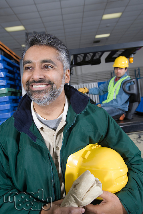 Cheerful man standing in factory