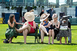 © Licensed to London News Pictures. 17/06/2014. Ascot, UK. Women sit on a bench.  Day one at Royal Ascot 17th June 2014. Royal Ascot has established itself as a national institution and the centrepiece of the British social calendar as well as being a stage for the best racehorses in the world. Photo credit : Stephen Simpson/LNP