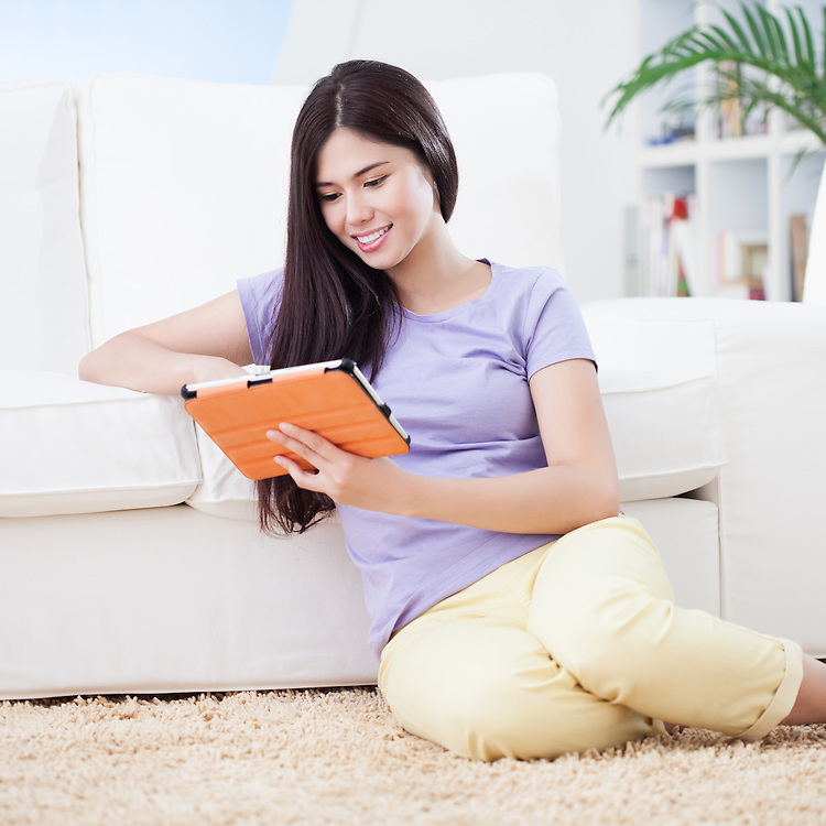 Beautiful smiling woman sitting on carpet in living room and using tablet pc.