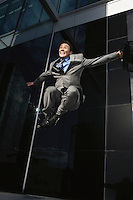 Businessman holding briefcase Jumping outside building low angle view