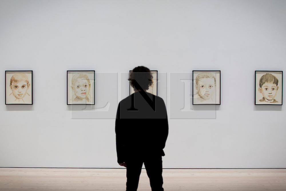 © Licensed to London News Pictures. 17/06/2013. London, UK. A Saatchi Gallery employee views a selection of 29 portraits of dictators as children by French artist Annie Kevans at the press view for a new exhibition taking place at the West London based gallery. The exhibition, which runs from the 18th of June to the 29th of September 2013 at the Saatchi Gallery, is entitled 'Paper' and aims to challenge the viewers perceived ideas and expectations of the material in a world where its use is becoming rare thanks to emails and the internet  Photo credit: Matt Cetti-Roberts/LNP