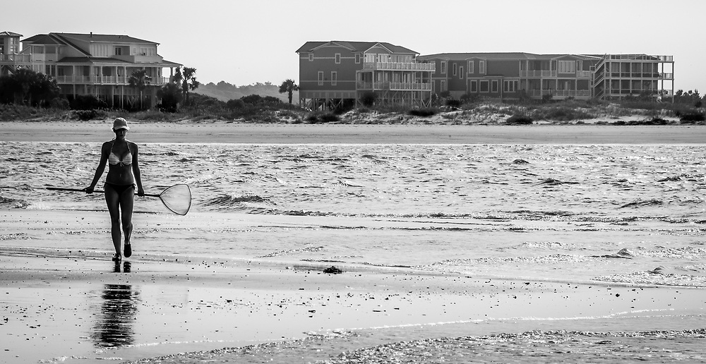 A young woman returns from morning explorations at low tide along the channel between Holden Beach & Ocean Isle Beach, NC.