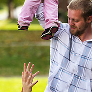 Neal Beck, 21, dangles his daughter, Harley Mattison, just out of reach of her mom, while they relax outside of their home in Henderson, Kentucky on October 17, 2012.