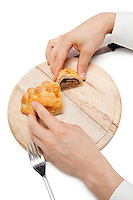Hands holding Cornish pastry cut into two pieces on wooden plate over white background