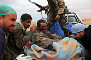 A wounded Libyan rebel, his leg shredded by shrapnel, is evacuated under heavy fire between rebel and pro-Qaddafi forces near Bin Jawad.The two sides are vying for control of the strategic road.