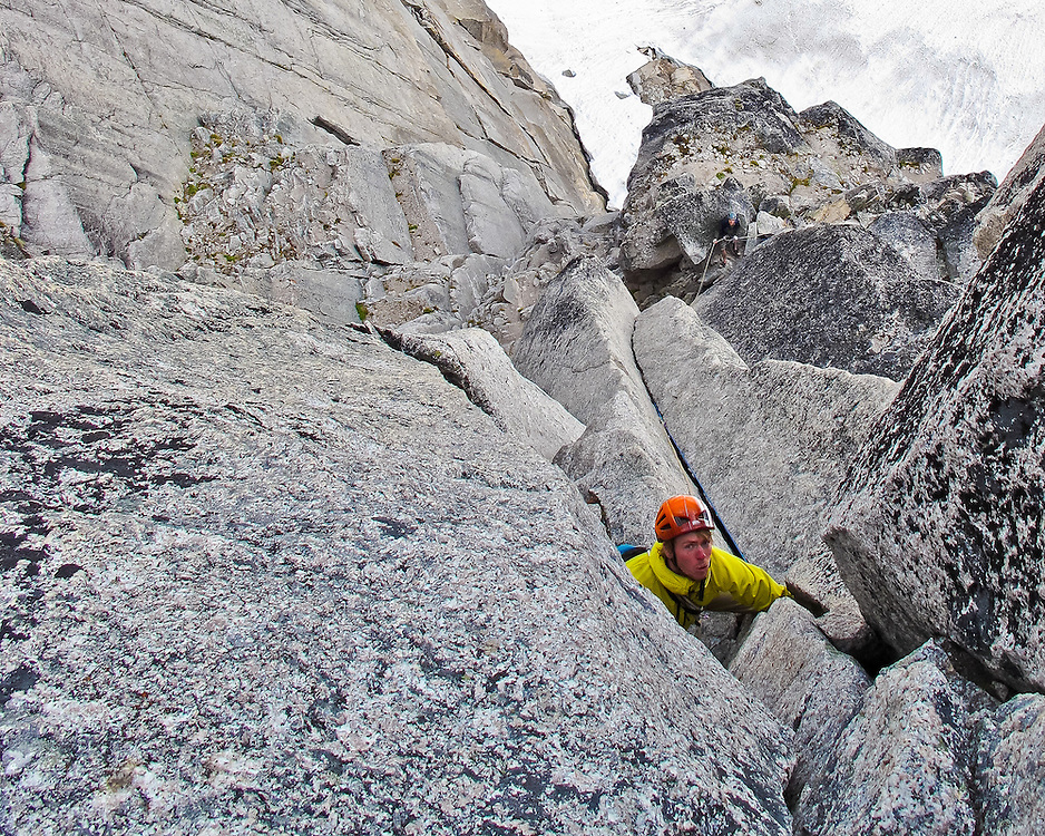 Tim, from the Netherlands climbs turns the second roof on the stellar 4th pitch of McTech Arete, 5.10a, on Crescent Spire, Bugaboo Provincial Park, British Columbia, Canada.