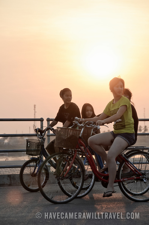 Vientiane locals ride their bikes in the late afternoon on the wide promenade along the banks of the Mekong River.