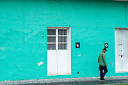 A man walks past a brightly painted Caribbean style building along the Venustiano Carranza in Tlacotalpan, Veracruz, Mexico. The tiny town is painted a riot of colors and features well preserved colonial Caribbean architectural style dating from the mid-16th-century.