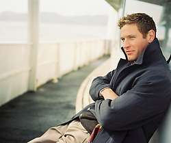 Blue eyed goodlooking man sitting on a ferry with his arms crossed