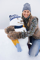 Woman embracing snowman kneeling on snow-covered hill portrait