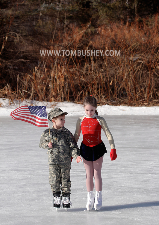 Livingston Manor, NY -Talon Miller, at left with the American flag, and his sister Suzanne stand on the ice at the 49th annual Livingston Manor Rotary Ice Carnival on Jan. 27, 2008. Talon, Suzanne and their mother Kimberlin Miller performed a tribute to their father, Maj. Joel Miller, who is serving in Iraq.