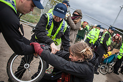 © Licensed to London News Pictures. 11/10/2017. Lancashire, UK.  A protester is dragged away from her child by police at the Anti-Fracking Demonstration in Kirby Misperton, Yorkshire. The protest blocked the entrance to Third Energy's Hydraulic fracking site after they were granted permission to set up their drilling rig at the site.  Photo credit: Steven Speed/LNP