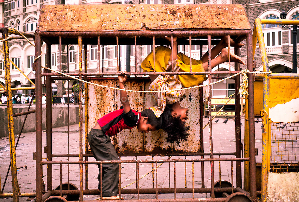 7th June 2013, Mumbai, India.   Children play inside a police barricade in the street near the Taj Mahal Palace Hotel, in Mumbai, India on the 7th June 2013<br /> <br /> PHOTOGRAPH BY AND COPYRIGHT OF SIMON DE TREY-WHITE<br /> <br /> + 91 98103 99809<br /> email: simon@simondetreywhite.com photographer in delhi photographer in delhi photographer in delhi