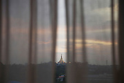 The iconic Shwedagon Paya seen through the curtains of a hotel room at duck.