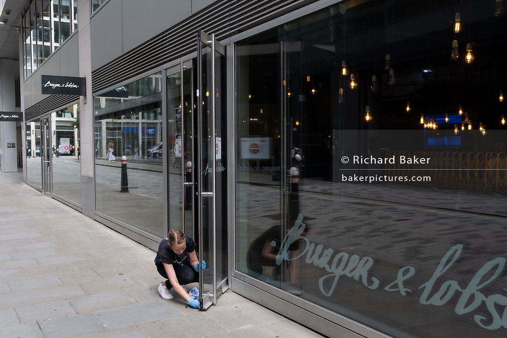 Readying to re-open a burger and lobster restaurant business, a females employee wipes down door surfaces during the Coronavirus pandemic in the City of London, the capital's financial district, on 6th August 2020, in London, England.