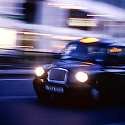 A London Black Cab speeds along at night.