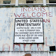 A sign warns unauthorized people to stay away from Alcatraz Island in San Francisco Bay. The red graffiti of Indians Welcome dates back to the occupation of Alcatraz by the group Indians of All Tribes in 1969-1971.