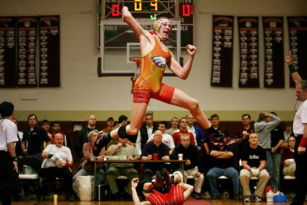 Franklin County High School wrestler, Hunter Adams (middle, top), jumps in the air after winning his 140lb match against Lord Botetourt High School wrestler, Jamie Carr, in overtime at the Big Orange wrestling tournament held at William Byrd High School in Vinton, Virginia. Adams stopped Carr's attempt at 4 consecutive Big Orange titles. Franklin County won the tournament 222 points to Grundy's 205 and 1/2 points.