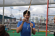 Instructor Zack Bodinger demonstrates how to clip in to the proper harnesses at Trapeze School New York during the June 4th morning class. The two hour beginner session taught the nine students in attendance the basics of flying trapeze -- including knee hangs and backwards somersaults -- in their facility on the roof of Pier 40...CREDIT: Daniella Zalcman for The Wall Street Journal.SLUG: NYMETROMONEY_Trapeze