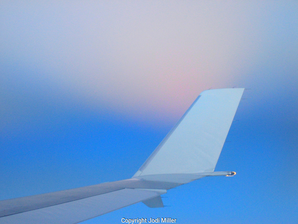 The wing of a small airplane against a pink and blue sky.