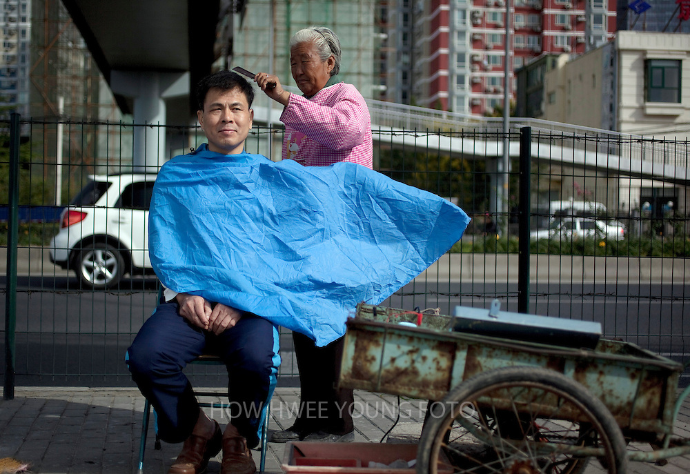 epa02922551 A Chinese man gets a haircut by a roadside barber in Beijing, China on 18 September 2011. Roadside barbers are a dying trade in the fast developing cities of China where a haircut still cost only 3RMB or 0.34 euros.  EPA/HOW HWEE YOUNG