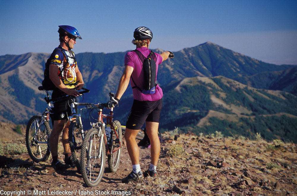Idaho, Smokey Mountains.  Couple mountain bikers take a brake to view terrain.