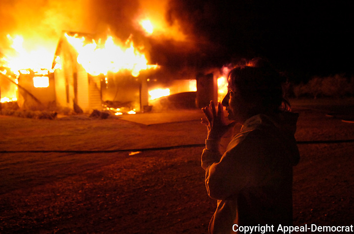 "Eva Woodard watches her house on Pass Road burn, Thusday, December 11,2008 in Sutter County. ""My daughter comes home from college tomorrow"" said Woodard."