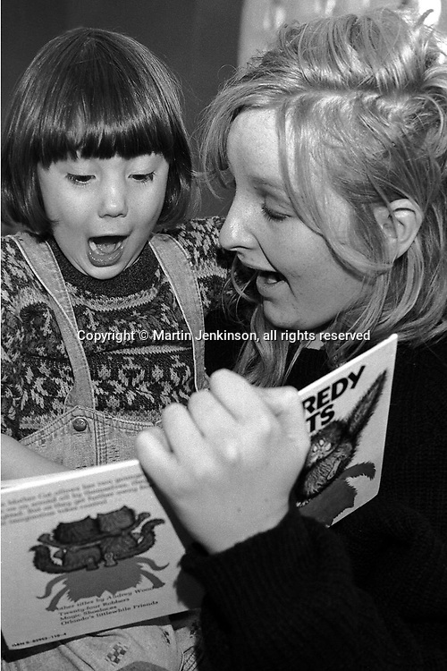 Nursery nurse helps a pre school child read a book....
