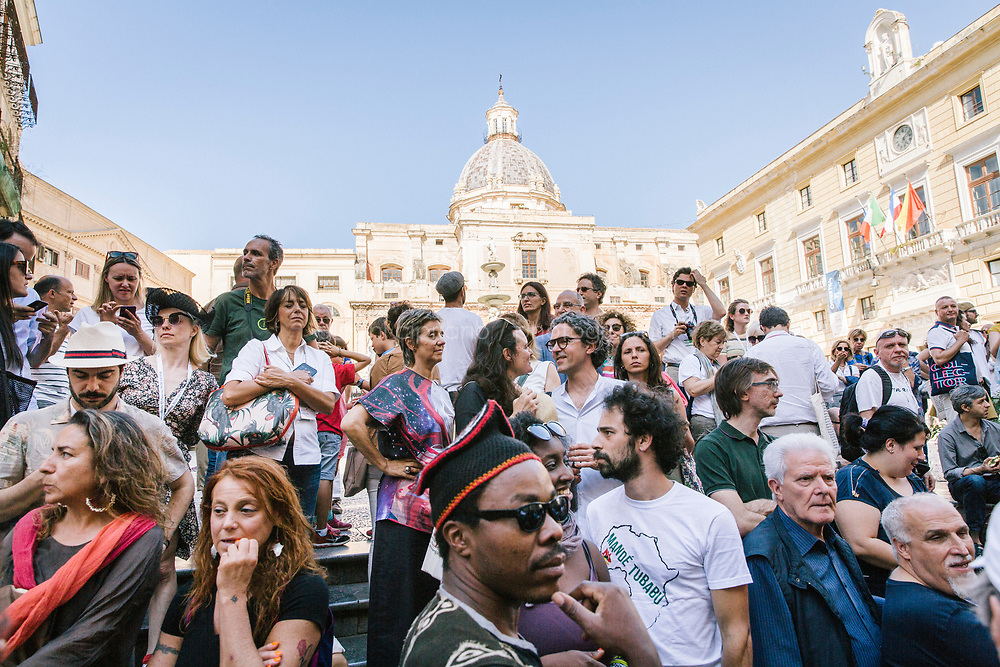 PALERMO, ITALY - 16 JUNE 2018: Visitors wait for Marinella Senatore's performance &quot;Palermo Procession&quot; to start at Manifesta 12, the European nomadic art biennal, in Palermo, Italy, on June 16th 2018.<br /> <br /> Manifesta is the European Nomadic Biennial, held in a different host city every two years. It is a major international art event, attracting visitors from all over the world. Manifesta was founded in Amsterdam in the early 1990s as a European biennial of contemporary art striving to enhance artistic and cultural exchanges after the end of Cold War. In the next decade, Manifesta will focus on evolving from an art exhibition into an interdisciplinary platform for social change, introducing holistic urban research and legacy-oriented programming as the core of its model.<br /> Manifesta is still run by its original founder, Dutch historian Hedwig Fijen, and managed by a permanent team of international specialists.<br /> <br /> The City of Palermo was important for Manifesta&rsquo;s selection board for its representation of two important themes that identify contemporary Europe: migration and climate change and how these issues impact our cities.