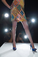 Low section of womans legs on catwalk with cameras flashing